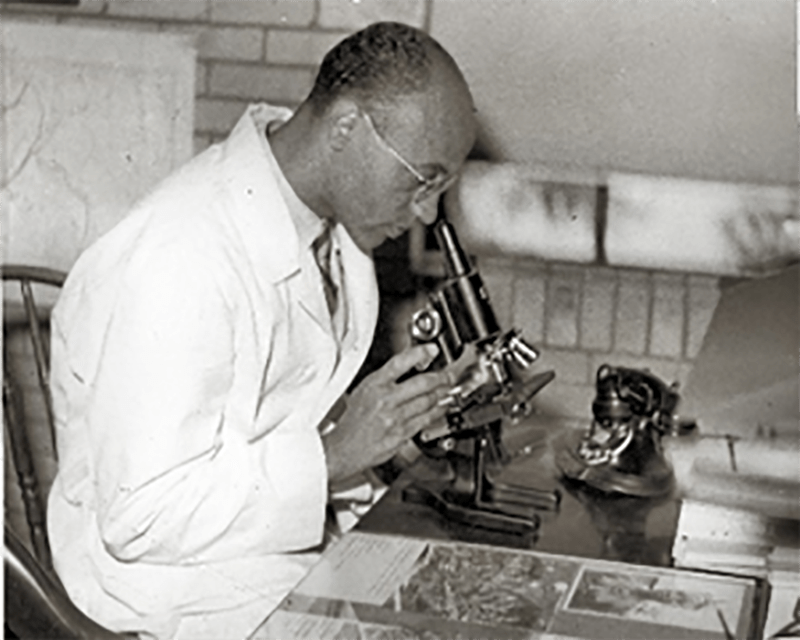 African American man looking into a microscope.