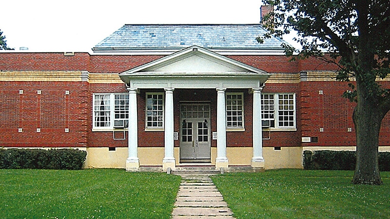 Photo of school with red walls and columns.